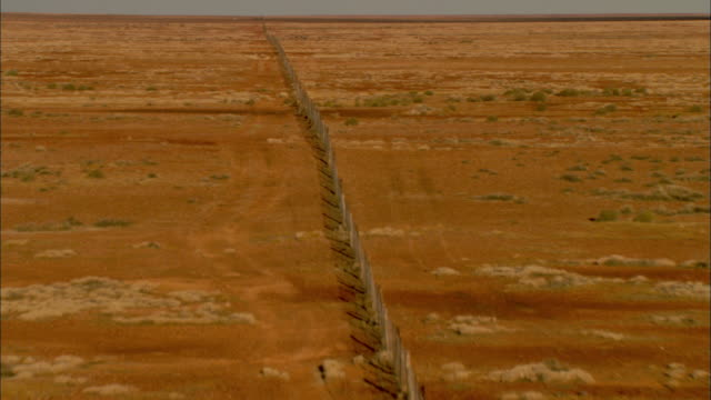a long fence stretches across a scrubland in australia. - shrubland stock videos & royalty-free footage