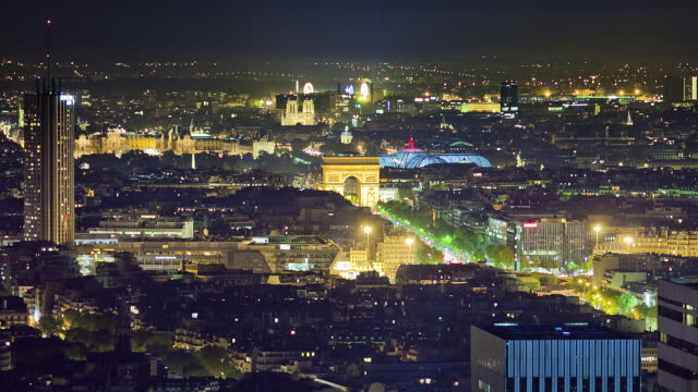 Long focal night shot over Paris from elevated view. Many public buildings visible : Arc de Triomphe, Louvre, Grand Palais, Notre Dame.