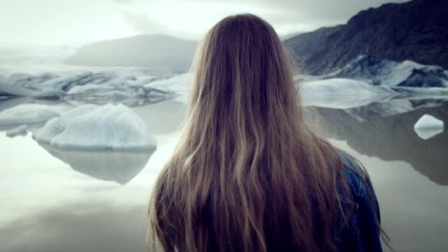 stockvideo's en b-roll-footage met lange haren meisje poseren op de gletsjer lagune. - roodhoofd