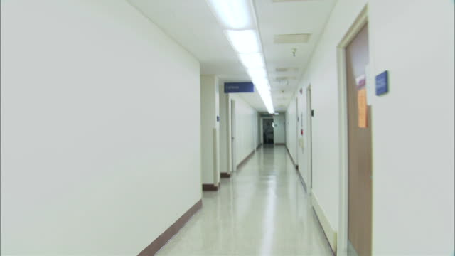 long hallway to cafeteria, bright with white walls and fluorescent light - white doorway stock videos & royalty-free footage