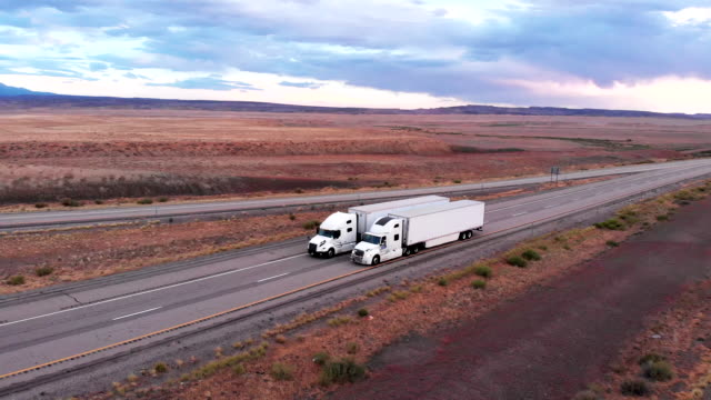 long haul freight hauler semi-truck and trailer traveling on a four-lane highway in a desolate desert at dusk or dawn - convoy stock videos & royalty-free footage