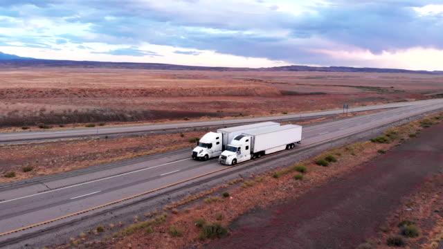 vídeos de stock, filmes e b-roll de semi-caminhão e reboque de carga de longa distância viajando em uma rodovia de quatro pistas em um deserto desolado ao anoitecer ou amanhecer - comboio