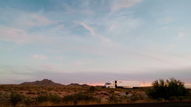long haul semi truck on a rural western usa interstate highway - trasporto merci via terra video stock e b–roll