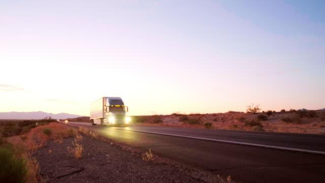 vídeos de stock, filmes e b-roll de caminhão semi longo do transporte em uma estrada interstate ocidental rural dos eua - caminhão