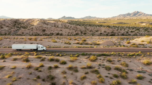 vídeos de stock, filmes e b-roll de caminhão semi de longo curso em uma rodovia interestadual rural oeste dos eua - comboio