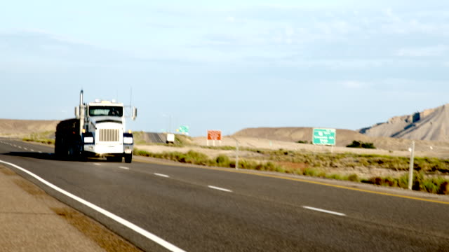 a long haul semi-truck and trailer heading down a four-lane highway in the desert at dawn or dusk - moving past stock videos & royalty-free footage