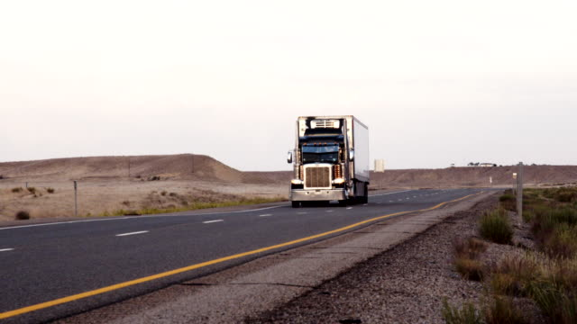 a long haul semi-truck and trailer heading down a four-lane highway in the desert at dawn or dusk - articulated lorry stock videos & royalty-free footage