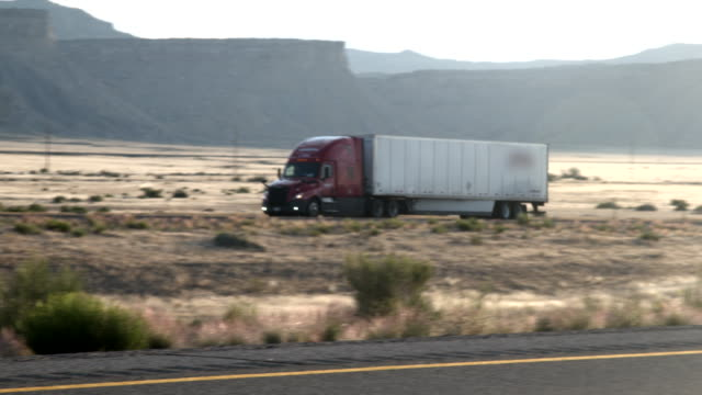 a long haul semi-truck and trailer heading down a four-lane highway in the desert at dawn or dusk - trucking stock videos & royalty-free footage
