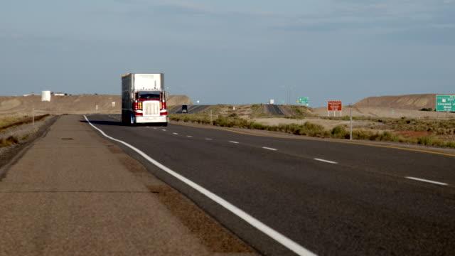 stockvideo's en b-roll-footage met een lange afstand semi-truck en trailer op weg naar een four-lane highway in de woestijn bij zonsopgang of zonsondergang - aanhangwagen