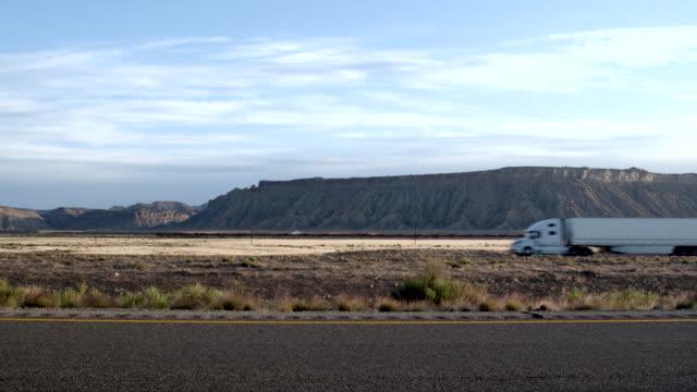 vídeos y material grabado en eventos de stock de un semi-truck y remolque de larga distancia que se dirige por una carretera de cuatro carriles en el desierto al amanecer o al anochecer - moving past