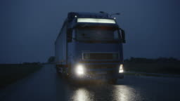 Long Haul Semi-Truck with Cargo Trailer Full of Goods Travels At Night on Freeway Road, Driving Across Continent Through Rain, Fog, Snow. Industrial Warehouses Area. Front Following Slow Motion Shot