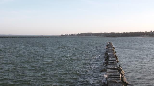 vídeos y material grabado en eventos de stock de long island sound breakwater sunset - vector
