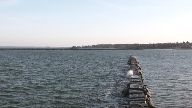 vídeos y material grabado en eventos de stock de long island sound breakwater waves, pan. - vector