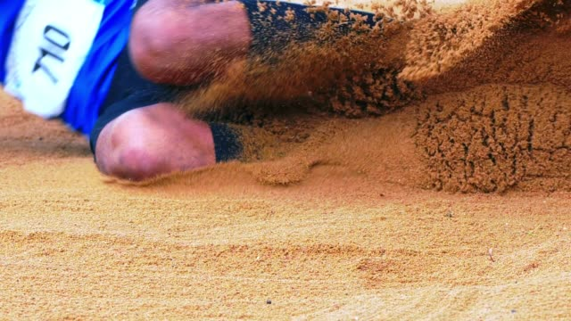 long jumper landing in sand pit - salto in lungo video stock e b–roll