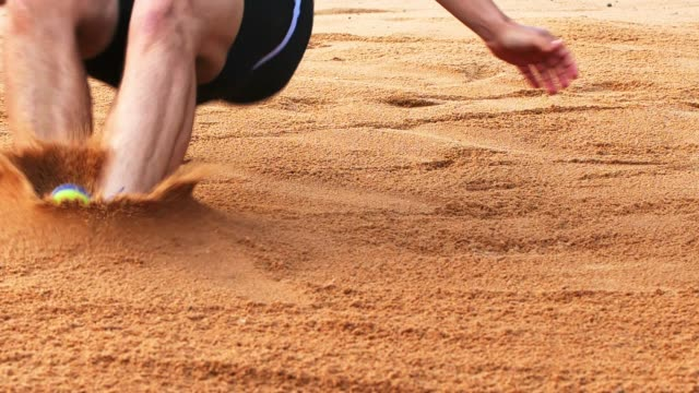 long jumper landing in sand - atletico video stock e b–roll