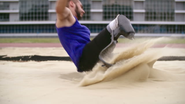 long jumper with prosthetic leg landing in sand - disability stock-videos und b-roll-filmmaterial
