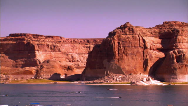 vídeos de stock, filmes e b-roll de long lens pan across million year old layers of rock that rim lake powell  in glen canyon national recreation area  / page, arizona, usa - lake powell