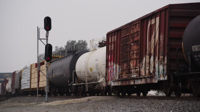 Long lens featuring a freight train and oil tankers rolling down the track with warning lights, past camera.