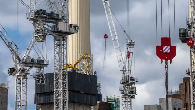 a long lens foreshortened closeup view of construction cranes and workmen working on the iconic chimneys on the battersea power station redevelopment - battersea stock videos & royalty-free footage