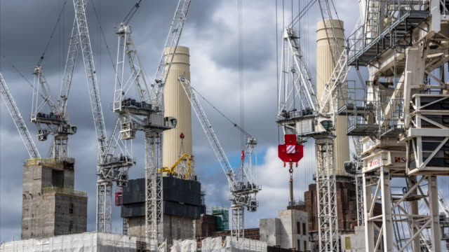 a long lens foreshortened closeup view of construction cranes working on the iconic chimneys on the battersea power station redevelopment - battersea stock videos & royalty-free footage