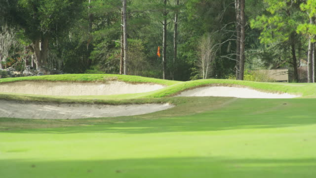 Long lens from the fairway of a golf course, three sand traps sit in front of the putting green.