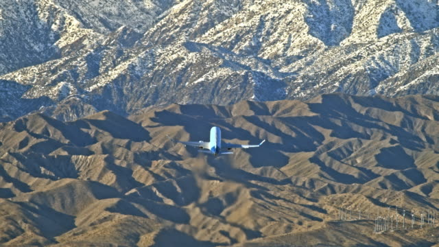 ws pan long lens rear view of jetliner after take off from airport fast climbing to higher altitude towards snow packed mountains and clouded upper skies - palm springs california stock videos & royalty-free footage