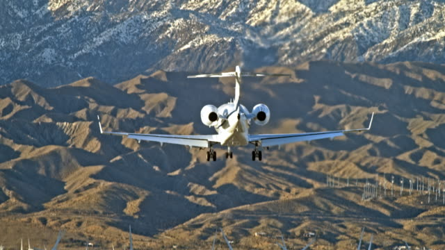long lens rear view of twin engine jetliner dropping into view against snow capped mountains as the aircraft rapidly descends and touches down on airport runway against backdrop of clean energy wind farm - palm springs california stock videos & royalty-free footage