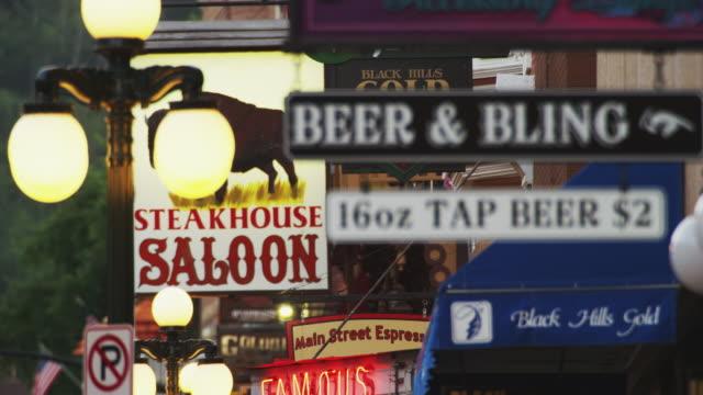 "vídeos de stock e filmes b-roll de long lens shot featuring an old fashioned streetlight and store signage on a main street, ""beer,"" ""bling,"" ""saloon."" - placa de nome de rua"