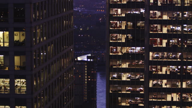 long lens slow pan up shot of office block at dusk - office block exterior stock-videos und b-roll-filmmaterial