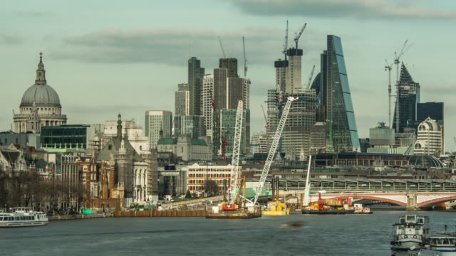A long lens tight frame of London's financial district and the dome of St Paul's Cathedral dappled sunlight and clouds pass overhead as construction cranes work on new building developments and river traffic passing along the Thames