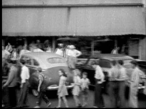 1945 ha ws pan long line in street leading to movie theater showing the tex ritter film tenting tonight on the old camp ground./ sylacauga, alabama - 1945 stock videos and b-roll footage