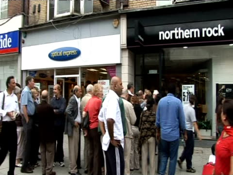long line of customers queue outside branch of northern rock to withdraw savings following company collapse; 2007 - banking stock videos & royalty-free footage
