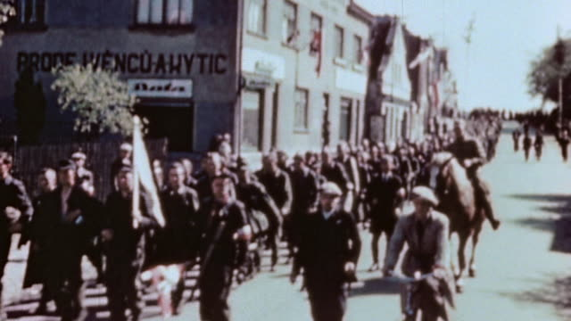 ha long line of german army soldiers under a white flag marching down village street / pilsen czech republic - recreational horse riding stock videos and b-roll footage