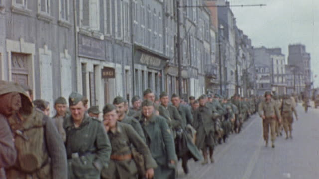 long line of german prisoners of war, including waffen ss officers and wounded in carts, marching along city street / aachen, germany - german military stock videos & royalty-free footage