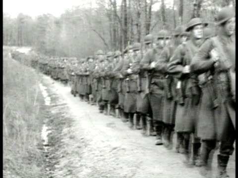 long line of infantry column marching on road. soldiers attacking dugout w/ flamethrower grenades . launching model airplane from catapult. firing... - 1941 stock-videos und b-roll-filmmaterial