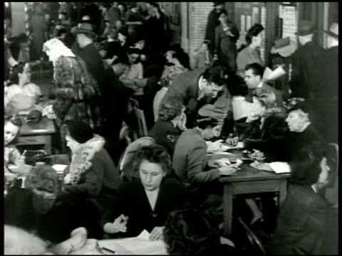 vídeos de stock, filmes e b-roll de long line of people in coats on sidewalk int room w/ people being helped at tables applying for ration books male hands tearing off top line of... - 1943