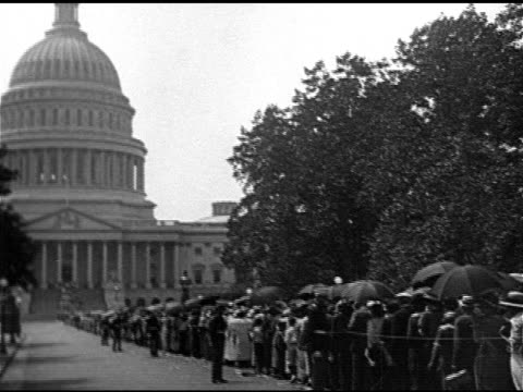 vídeos de stock, filmes e b-roll de long line of people some w/ umbrellas outside up into capitol rotunda ms people women children moving into rotunda ms president warren g harding's... - 1923