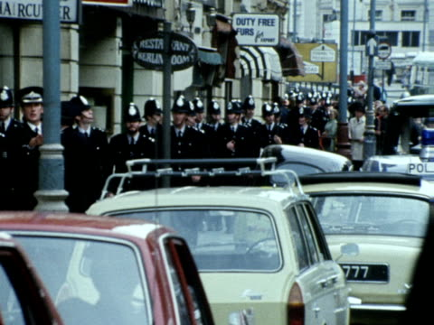 vídeos de stock e filmes b-roll de a long line of policemen walk along a knightsbridge street towards the spaghetti house restaurant where seven people are being held hostage by three... - setembro