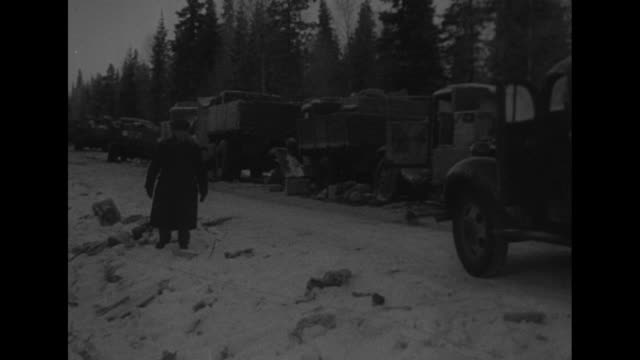 PAN long line of Soviet military trucks bogged down in the snow as Finnish military truck drives by / MS stalled Soviet truck / MS truck trailer...