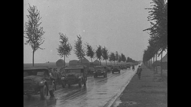 stockvideo's en b-roll-footage met long line of trucks moves down road in rain as british forces move to french front during world war ii / scottish military band wearing raincoats... - british military