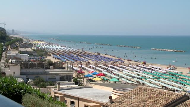 ws long line of umbrellas on beach / termoli, molise, italy - affollato video stock e b–roll