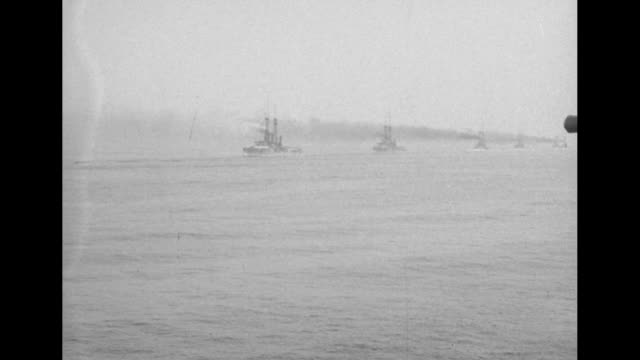a long line of warships of the atlantic fleet steams off the coast of connecticut / crew members with two twelveinch guns on turret move left /... - passing a note stock videos and b-roll footage
