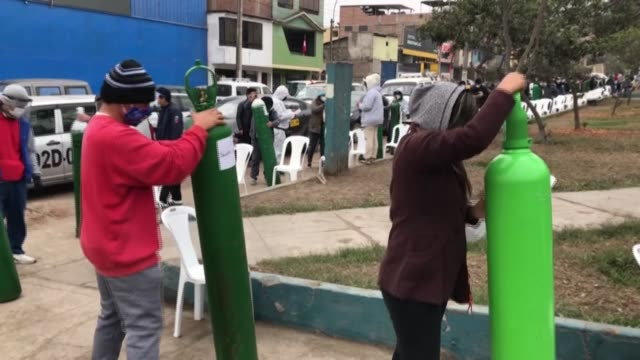 stockvideo's en b-roll-footage met long lines of peruvians take empty oxygen bottles to a mobile unit run by the army in lima to get a refill as their loved ones battle against covid19 - peruaanse etniciteit