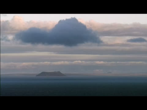 stockvideo's en b-roll-footage met long locked down shot of clouds over islet in pacific ocean / galapagos islands - galapagoseilanden