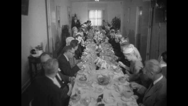 long luncheon table with seated guests / prince albert seated next to audrey hepburn, frank sinatra stands behind talking to them / donald oõconnor... - audrey hepburn stock videos & royalty-free footage