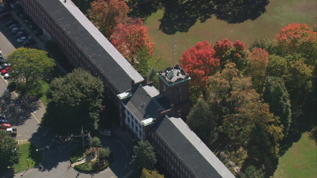 AERIAL Long narrow building with tower in business district, with fall trees and lawns in park / Springfield, Massachusetts, United States