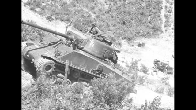 Long pan of mountainous Korean territory / VS US M4 Sherman tank rolling up steep incline with it firing then explosion in far distance / Note exact...