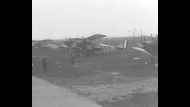 Long pan shot of hangars at training facility used to train aviators for WWI duty / drive by shot of lines of planes on field / pan shot students...