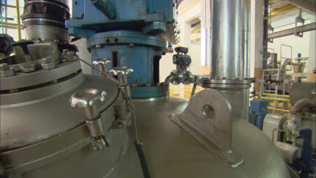 long pipes lead to a chocolate mixer at a chocolate factory in malaysia. - bolt stock videos & royalty-free footage