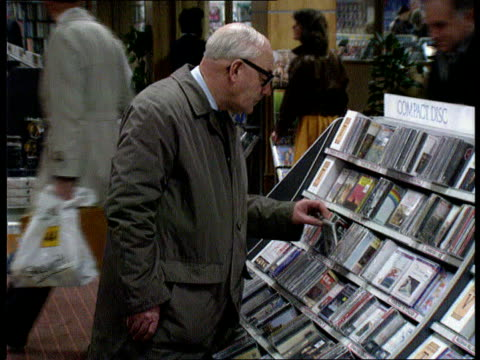 Long playing records W H Smith MS SIDE man looking at compact disc MS SIDE another looking at cassettes MS SIDE two young girls looking at tapes R...